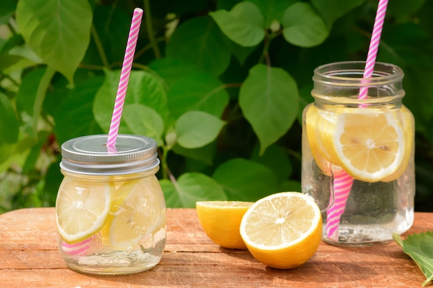 Two jars with lemonade and pink straws