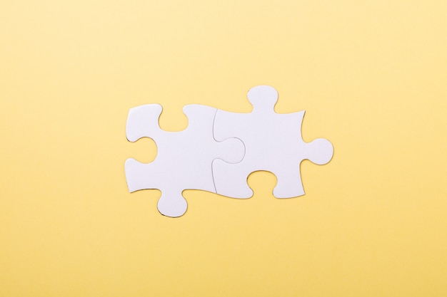 Two jigsaw puzzle pieces on yellow
