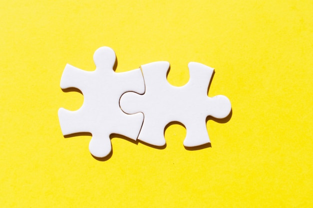 Two jigsaw puzzles pieces on illuminating yellow background