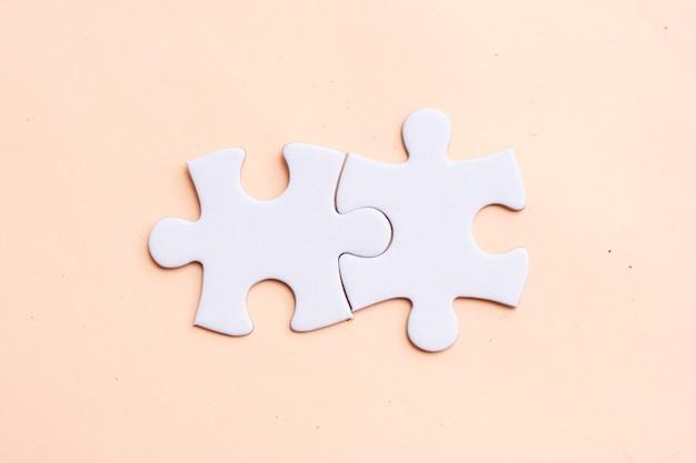 ピンクの背景に2つのジグソーパズルのピース