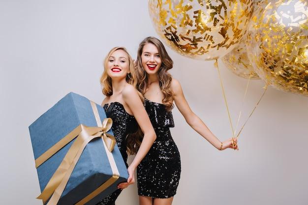 Две радостные модные молодые женщины в роскошных черных платьях празднуют день рождения на белом пространстве. веселая, элегантная, улыбающаяся, настоящая эмоция, золотые шары.
