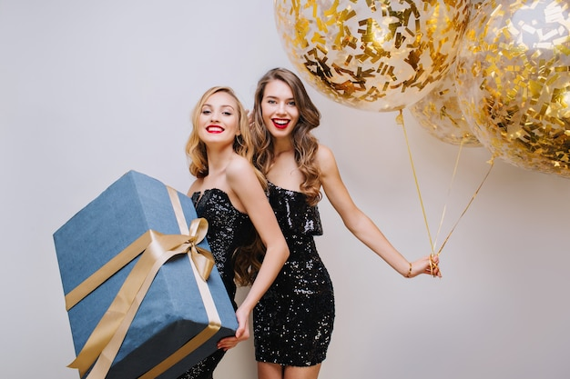 Two joyful fashionable young women in luxury black dresses celebrating birthday party on white space. having fun, elegant look, smiling, true emotionsgolden balloons