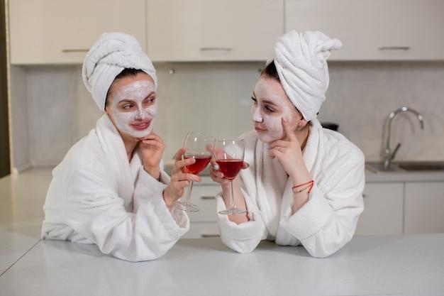 ローブの2人の楽しいガールフレンドは週末の飲み物赤ワインの家のインテリアの若者と楽しいコンセプトの高品質の写真を祝います