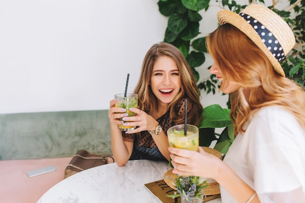 Two joyful girls sharing gossips after work and laughing, while chilling in stylish cafe