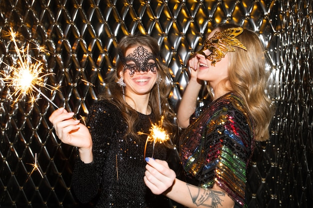 Two joyful girls in venetian masks holding sparkling bengal lights while having fun at party in the night club