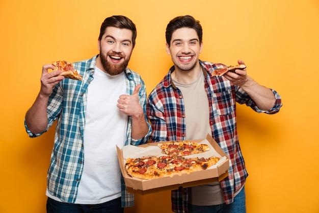 Два радостных мужчины, держащие пиццу, пока бородатый мужчина показывает большой палец на желтой стене