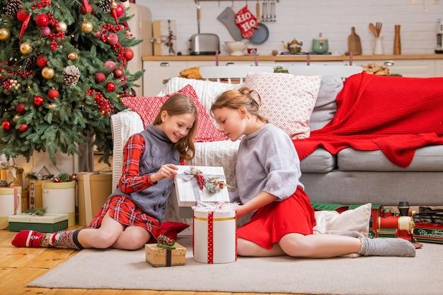 2人のうれしそうな姉妹がクリスマスツリーの近くの家に座って、贈り物の入った箱を見ています