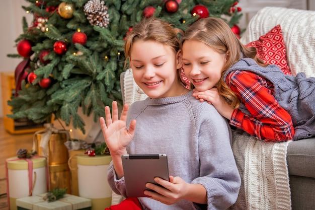 2人のうれしそうな姉妹が家でクリスマスツリーの近くに座ってタブレットモニターを見ています