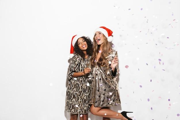 白いスペースに隔離された新年を祝う赤い帽子をかぶった2人の楽しいスマートな服装の女の子