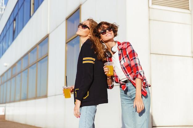 Two joyful teenage girls in sunglasses drinking