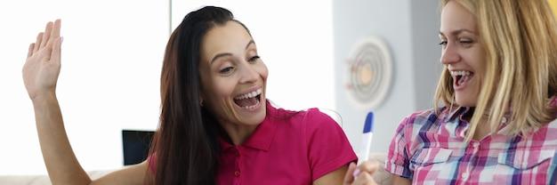 2人の楽しい女性がソファに座って妊娠検査を行っています。家族のコンセプトで補充を待っています