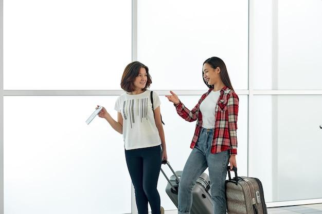 出発前に空港で荷物とチケットを持つ2人のうれしそうな女性。休暇や旅行の前に話したり笑ったりします。