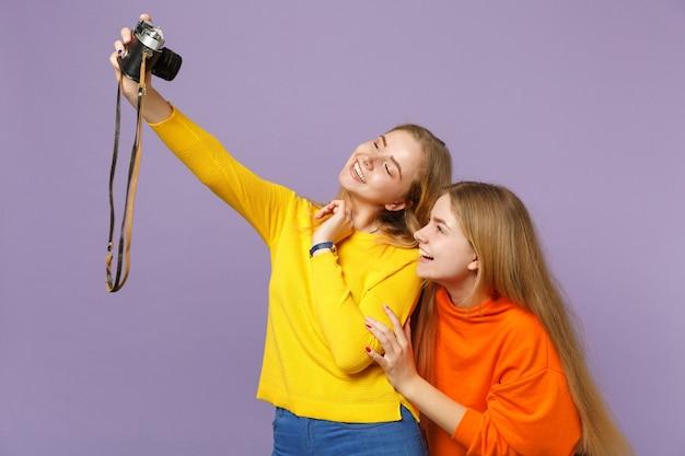 Две радостные молодые блондинки сестры-близнецы в яркой одежде делают селфи на ретро-винтажной фотоаппарате, изолированной на фиолетовой синей стене. концепция семейного образа жизни людей.