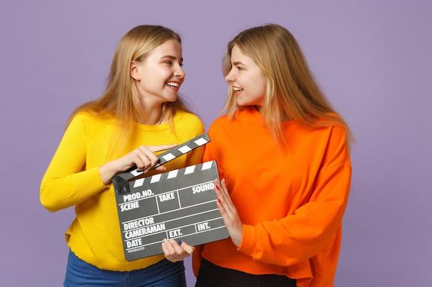 두 즐거운 젊은 금발 쌍둥이 자매 여자 화려한 옷을 입고 클래식 블랙 영화 만들기 clapperboard 바이올렛 파란색 벽에 격리. 사람들이 가족 라이프 스타일 개념.