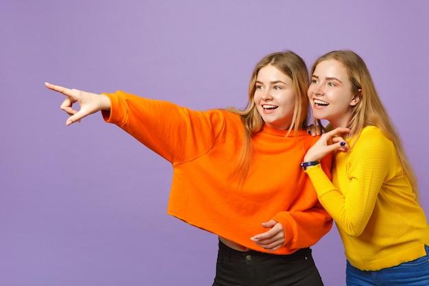 パステルバイオレットブルーの壁に隔離された人差し指を脇に向けて鮮やかなカラフルな服を着た2人の楽しい若いブロンドの双子の姉妹の女の子。人々の家族のライフスタイルの概念。