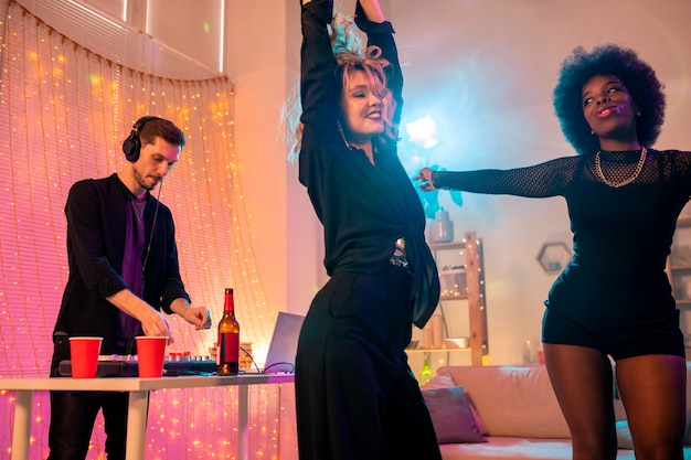 Two joyful young intercultural females in black attire enjoying dance at home party while guy with headphones mixing sounds