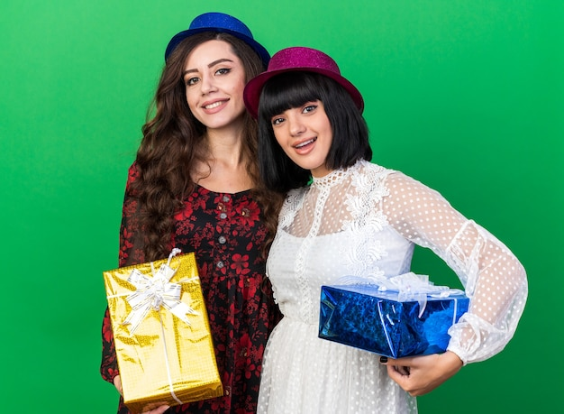 Two joyful young party girls wearing party hat both holding gift package isolated on green wall