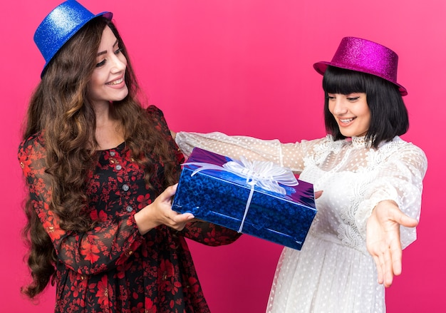 Two joyful young party womans wearing party hat one looking at her friend giving her gift package another girl spreading hands looking at package isolated on pink wall