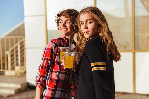 Two joyful young teenage girls in sunglasses