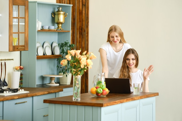 Two joyful young women making online video call on laptop, waiving hands and laughing