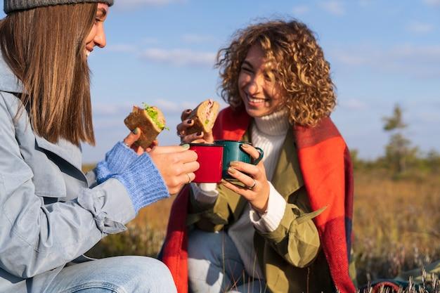 화창한 가을날 야외에서 피크닉을 하는 두 명의 즐거운 젊은 여성이 샌드위치를 먹고 뜨거운 차나 커피를 마신다