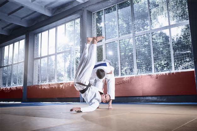 Two judo fighters showing technical skill while practicing martial arts in a fight club