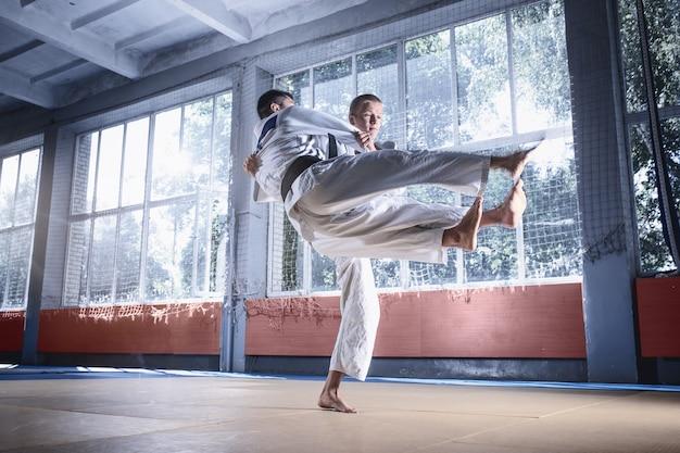 ファイトクラブで武道を練習しながら技術力を発揮する柔道ファイター2名。二人は制服を着た男性に合いました。戦い、空手、トレーニング、芸術、アスリート、競争の概念