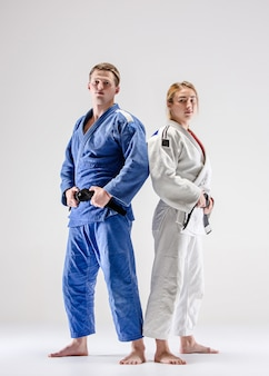 The two judokas fighters posing on gray