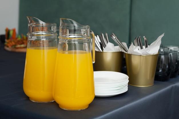 オレンジ色の飲み物の2つの水差し。お祝いのテーブル、オレンジジュースを提供しています。