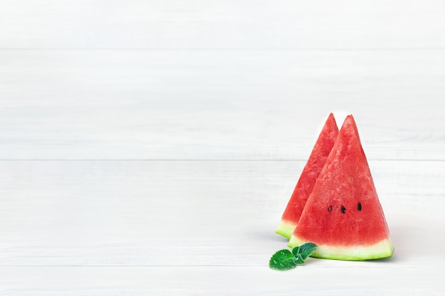 Two juicy slices of ripe watermelon with a mint leaf on a white table.