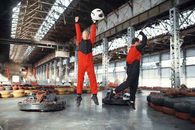 Two kart racers celebrates victory, karting auto sport indoor.