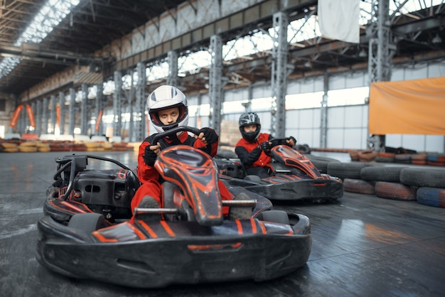 Two kart racers enters the turn, front view, karting auto sport indoor.