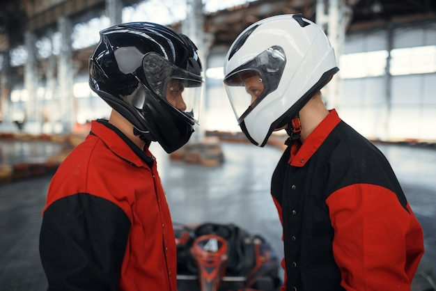 Two kart racers in helmets standing face to face