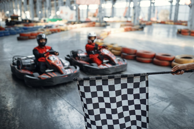 Два картинга на стартовой линии, клетчатый флаг, вид спереди, картинг автоспорт в помещении. скоростная гонка на тесной картинговой трассе с шинным барьером. соревнования на быстрых автомобилях, отдых с высоким уровнем адреналина