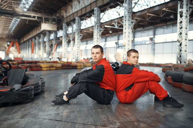 Two kart racers sitting back to back on the ground, karting auto sport indoor.