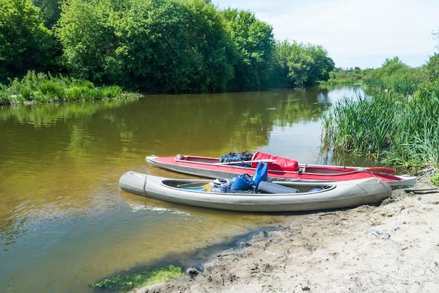 아무도 없는 강둑 근처 물에 서 있는 두 개의 카약