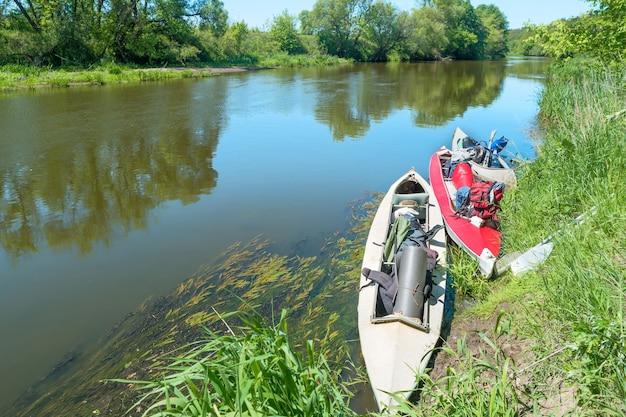 Две каяки стоят в воде у берега реки без людей