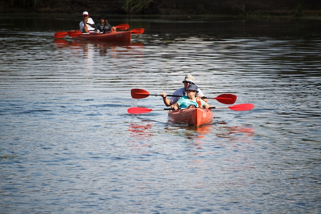 Two kayaks with double oarsmen ride along a calm river, the concept of active recreation on the river