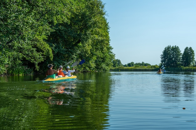 Two kayaks with a group of several people rowing. rafting on the fast river. adventure traveling lifestyle. concept wanderlust. active weekend vacations wild nature outdoor. the canoeing.