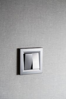 壁に灰色の2つのキースイッチプラスチック製の機械式スイッチ。修理後に取り付けられたライトスイッチ。省エネの概念。横にコピースペースがあるライトスイッチのクローズアップ