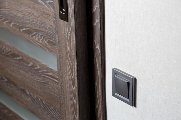 ドアの近くの灰色の2つのキースイッチ、プラスチック製の機械式スイッチ。ライトスイッチは修理後に取り付けられます。省エネコンセプト。ライトスイッチを閉じる