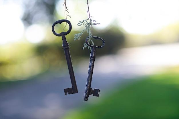 Два ключа от старинного загородного дома на естественном фоне