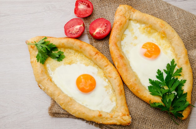 Two khachapuri with egg, parsley and tomatoes on sackcloth, top view