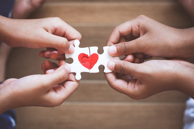 Two kid hands connecting couple jigsaw puzzle piece with drawn red heart