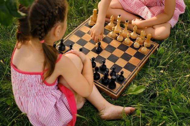 2人の子供が古い木製のチェス盤でチェスをしています