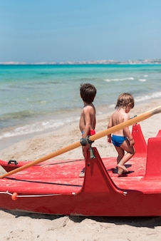 Two kids at the beach standing on paddle boat