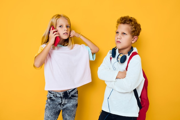 Two kids boy and girl looking into a smartphone and playing games yellow background