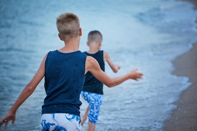 Two kids boys walking on sea beach summer, happy best friends playing.