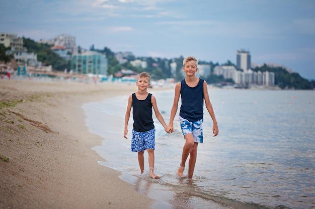 Two kids boys walking on sea beach summer, happy best friends playing