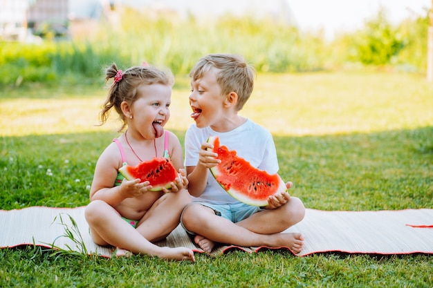 Two kids eat watermelon on back yard. kids eat fruit outdoors. healthy snack for children. toddlers show tongue to each other